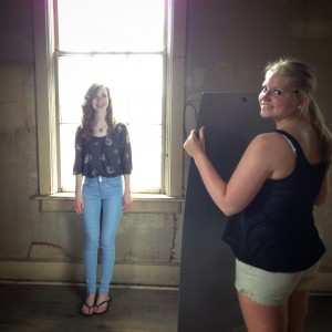 Photographer's assistant, Danielle, holds a plexiglass mirror for Hannah's senior pictures in our retro ballroom set.